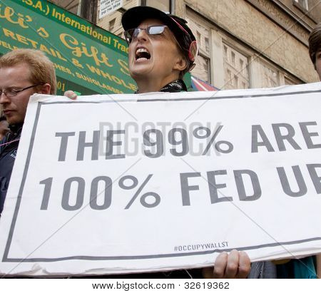 NEW YORK - MAY 1: A protester holds a sign that reads 'The 99% Are 100% Fed Up ' during the march to Union Square from Bryant Park at Occupy Wall St 'May Day' protests on May 1, 2012 in New York, NY.