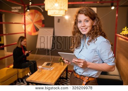 Young cheerful office manager with digital tablet standing in front of camera while preparing for presentation in working environment