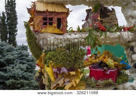 Colorful Autumn Display On An Old Stone Wall With Quaint Little Cottage, Dried Leaves, Pine Cones An