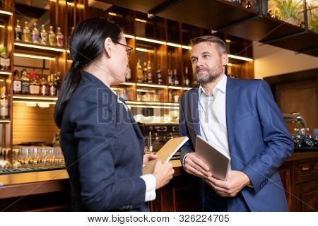 Two owners of luxurious restaurant standing by bar counter and consulting about some working moments