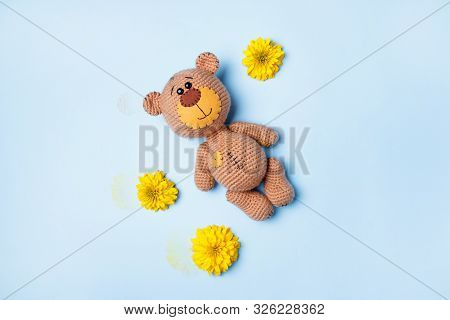 Amigurumi Handmade Teddy Bear With Yellow Chrysanthemum Isolated On A Blue Background. Baby Backgrou