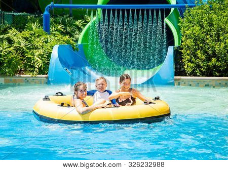 Family having fun together a water park. Riding on an inflatable tube together on a water slide.