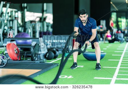 Sporty Caucasian Man Exercising With Battle Ropes At The Gym On Green Floor. Strong Male Determine W