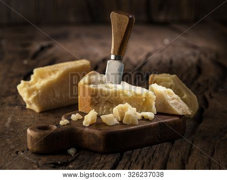 Piece of Parmesan cheese and cheese knife on the wooden board. Dark background.