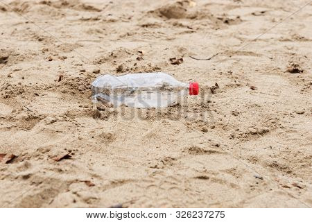 Discarded plastic water bottle lies in the sand on a beach poster