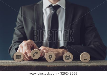 Placing Five Wooden Circles With Contact And Information Icons In A Row
