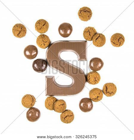 Chocolate Letter S With Bunch Of Scattered Chocolate Pepernoten Cookies From Above On White Backgrou