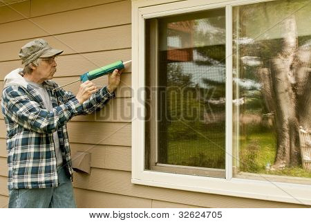 Man Using A Caulking Gun