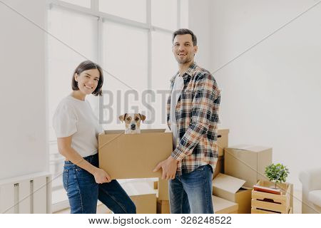 Happy Family Couple Hold Carton Box With Small Puppy, Stand Indoor Against Big Window, Glad To Becom