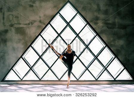 Young Beautiful Woman Doing Yoga Asana Toe Pose Variation On Large Triangular Window Background. Pra