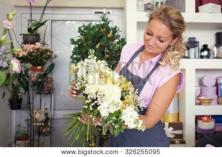Working In Flower Shop. Professional Florist Is Creating Huge Beautiful Bouquet From Fresh White Ros
