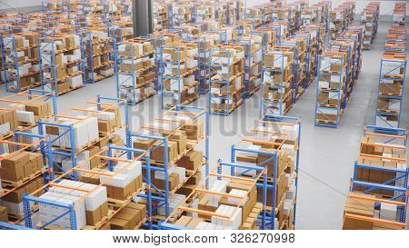 Warehouse With Cardboard Boxes Inside On Pallets Racks, Logistic Center. Huge, Large Modern Warehous