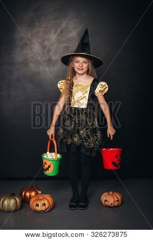 Cute girl in Halloween costume standing with full candy collectors and stylish Jack o lanterns on black background poster