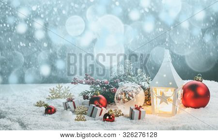 Christmas holidays card with gifts , balls , and glowing lantern in snow