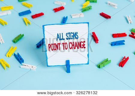 Conceptual hand writing showing All Signs Point To Change. Business photo text Necessity of doing things differently new vision Colored clothespin papers empty reminder blue floor officepin. poster