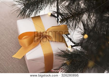 Find Your 2020 Gift. Christmas Present With Gold Ribbon Under Pine Tree