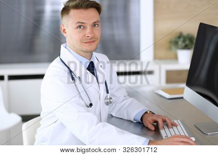 Doctor Man Sitting Behind A Computer At Workplace In Clinic Or Hospital Office. Medic Headshot And M