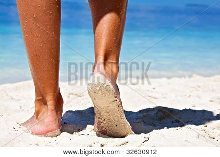 Women's legs on a sandy beach Maldives poster