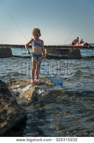 Little Girl Standing On Pier With Fishing Net In Hand