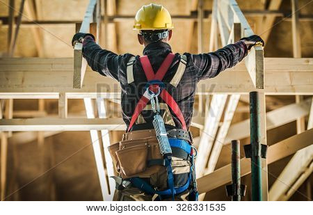Wood House Construction Challange. Caucasian Carpenter Contractor Wearing Safety Harness In Front Of