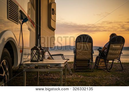Scenic Rv Campsite Pitch. Camper Van In The Recreational Vehicles Park. Woman Relaxing On A Chair An