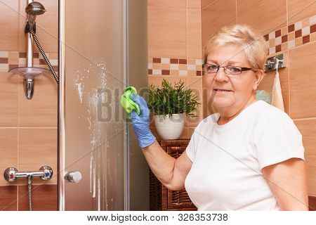 Senior woman in protective rubber gloves using green microfiber cloth for washing and cleaning shower glass, concept of household duties poster