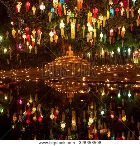 Buddha Image Surrounded By Candles And Colourful Lanterns. Beautiful Golden Buddha Image Lit By Cand