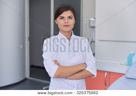 Portrait Of Confident Young Female Medic With Arms Crossed Over Clinic Interiers