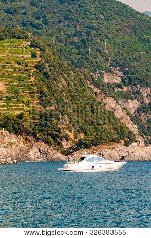 Monterosso Al Mare, Italy - September 02, 2019: Sea Yacht Near The Rocky Coastline With Vineyard, Ol