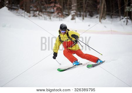 Young skier performing skiing trick. Ski training during snowfall. Carving skiing technique. Winter activities, freestyle, adventure, thrill concept poster