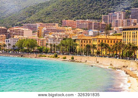 Ajaccio Public Beach With Tourists At Sunny Day. Summer Landscape Of Corsica Island At Sunny Summer