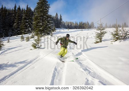 Male Person Skiing On Wide Open Ski Runs In Downhill. Skiing Down Between Fir Trees. Spending Time T