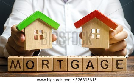 Wooden Blocks With The Word Mortgage And Businessman. The Concept Of Buying A Home On Credit. Loan F