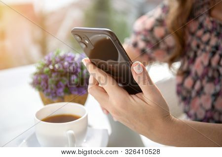 Anapa, Russia - October 4, 2019: Woman Hand Holding Apple Iphone 11 And Sitting At The Table. Iphone