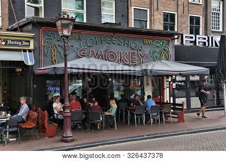 Amsterdam, Netherlands - July 10, 2017: People Visit A Coffee Shop In Amsterdam, Netherlands. Coffee