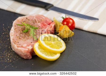 Fresh Pork Steak For Making The Steak Menu Is A Popular Food In Europe With Lemons, Grapes, Tomatoes