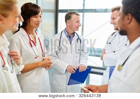 Doctors and nurses in a team meeting together with the senior physician