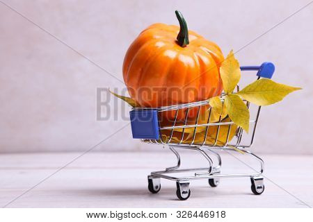 Pumpkin And Dry Leaves In Supermarket Trolly On Neutral Background. Concept Halloween. Copy Space.