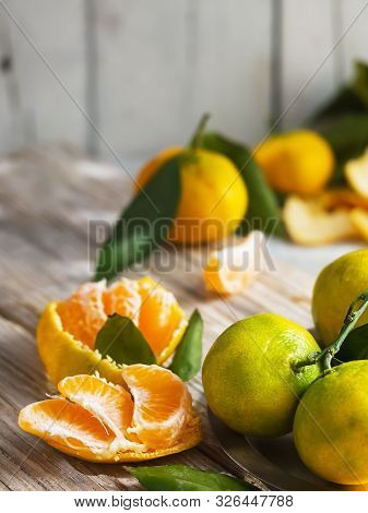 Fresh, Juicy Tangerines With Leaves On A Light Wooden Vintage Surface. Nearby Are Pieces Of Peeled T