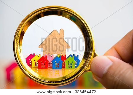 Business Man Use Magnifying Glass Search And Explore Real Estate, Houses, Apartments For Investment.