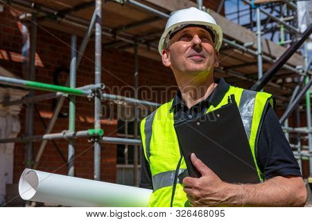 Thoughtful middle aged man, male builder foreman, worker, contractor or architect on construction site holding black clipboard and architectural plans