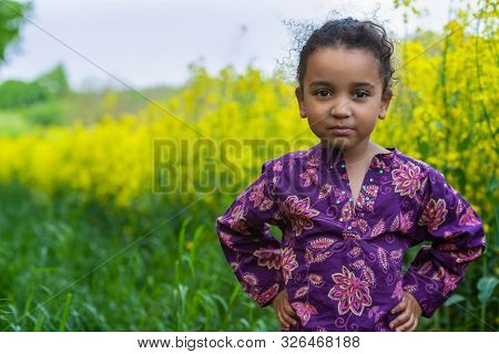 Beautiful happy cheeky mixed race female African American girl child standing hands on hips smiling outdoors in in field of yellow flowers
