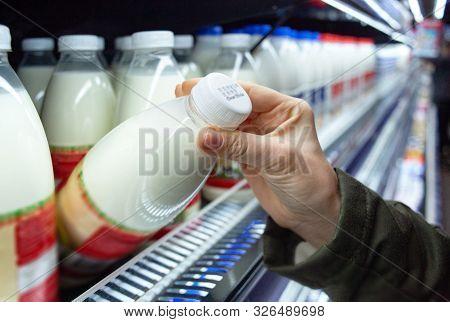 Womans Hand Holding Milk Bottle In Supermarket. Man Shopping Milk In Grocery Store. Man Checks Produ