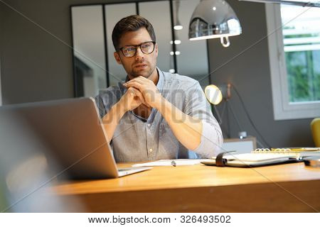 Middle-aged man working on laptop in office