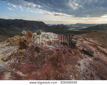Colorful rhyolit red and orange fumarole at foot of Brennisteinsalda mountain with panorma of Landmannalaugar. Area of Fjallabak Nature Reserve in Highlands of Iceland poster