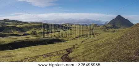 Panoramic volcanic landscape of green Storasula mountain with lush moss, footpath and blue creek water between Emstrur and Alftavatn camping sites on Laugavegur trek in area of Fjallabak Nature Reserve, Iceland poster