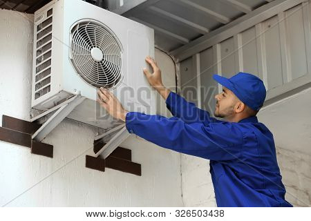 Professional Technician Maintaining Modern Air Conditioner Outdoors
