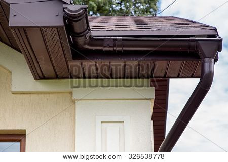 Brown Plastic Drainage Gutter On A Roof With Bituminous Tiles Close Up Of The House Drainage Pipes.