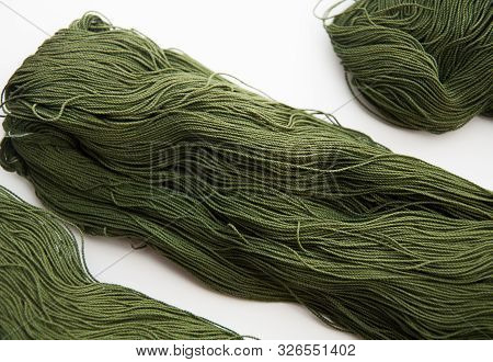 Closeup Of Fine Gauge Yarn Olive Green Isolated On A Light Background.  This Skein Or Hank Of Yarn I