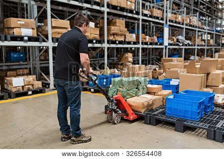 Warehouse Worker Dragging Hand Pallet Truck Or Manual Forklift With The Shipment Pallet Unloading In